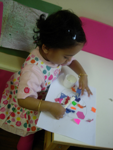 Girl building a collage at Early Learners Nursery School, Leicester