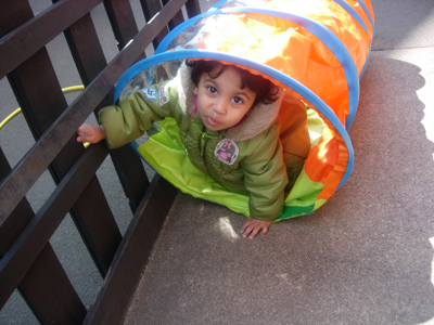 Girl in a play tunnel outside at Early Learners' Nursery School, Leicester