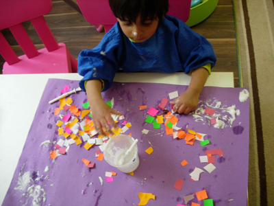 Making a colourful collage with glue at paper Early Learners' Nursery School, Leicester