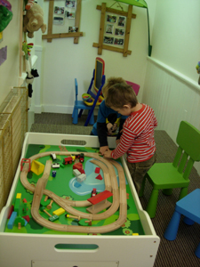Pre-school children playing with a train set at Early Learners Nursery School, Leicester