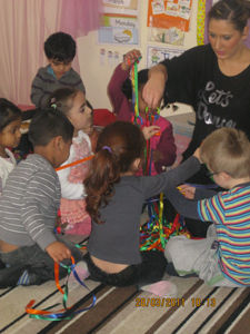 Pre-school children with their keyworker, playing with ribbon