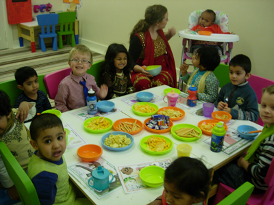 Pre-school children eating together at Early Learners' Nursery School, Leicester